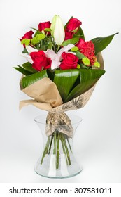 Flower arrangement bouquet composed of roses and lily in a transparent vase, lateral view, on white background
