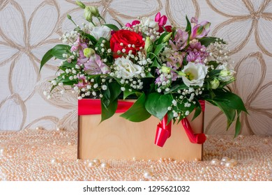 Flower arrangement in a box with a background of pearls