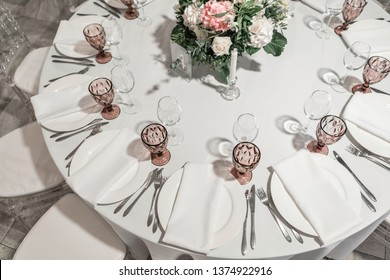 Flower arrangement in the center of the table. Interior of restaurant for wedding dinner, ready for guests. Round Banquet table served. Catering concept.