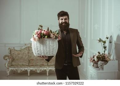 Flower arrangement concept. Bearded man hold basket with flower arrangement. Man with flower arrangement in floral shop. Bouquet of roses in flower arrangement.