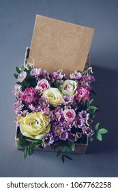 Flower arrangement in a design box with a business card, on a gray background