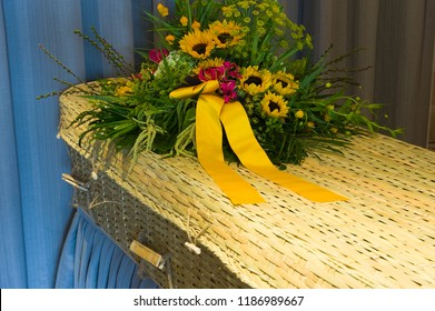 A flower arrangement on a braided coffin in a mortuary