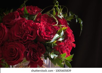Flower arrangement of red roses, close-up, with black background
