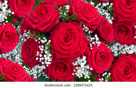 Flower arrangement of red roses with white gypsophila in close-up