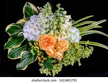 Flower arrangement of roses, foxgloves, hydrangeas, euphorbia, hosta and Liriope muscari leaves
