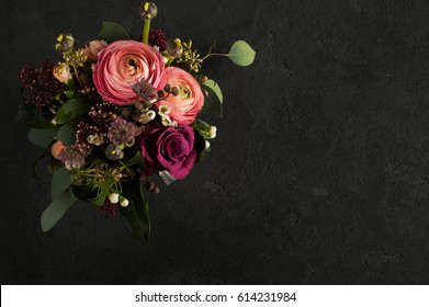 Flower arrangement of roses and ranunculus on black concrete background.  Greeting card concept, copy space for text