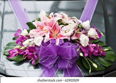 Flower arrangement tied to a wedding car