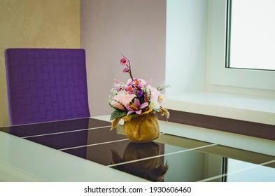 flower arrangement in vase on dining table. Stylish kitchen interior.