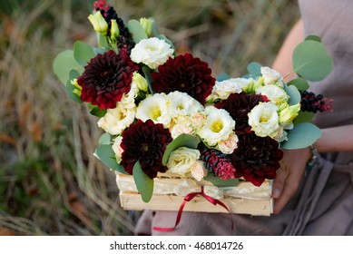 Flower arrangement in a wooden box in the hands of the florist