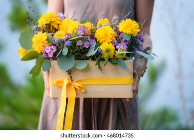 Flower arrangement with yellow and purple flowers in a wooden box in the hands of a florist in the park in autumn day