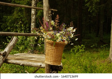 Flower basket in the forest hanging on wooden poles, gree grass, hunter place