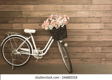 flower in basket of vintage bicycle on vintage wooden house wall