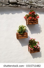 Flower baskets in front of white house wall in an Italian village