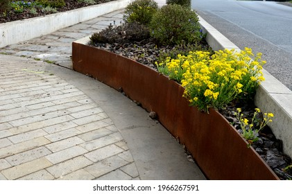 the flower bed is bordered by a rusty sheet metal design. perennials bloom in the flowerbed. paving of stones between two flower beds.