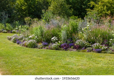 Flower bed surrounded by green lawn in a botanical garden