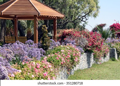 Flower beds of different colors in the background of a wooden gazebo