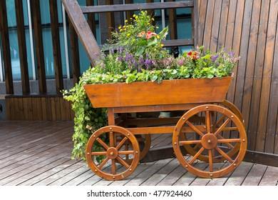 Flower bed-wheelbarrow wooden decoration in a garden