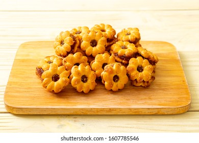 flower biscuits with pineapple jam on wood background