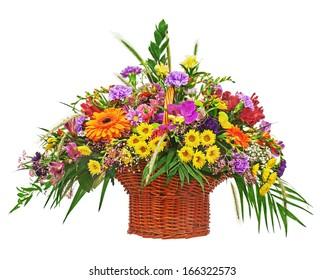 Flower bouquet arrangement centerpiece in wicker basket isolated on white background. Closeup.