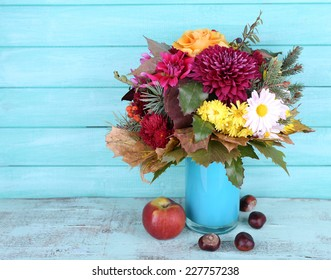 Flower bouquet in blue vase and apple on table on blue wooden wall background