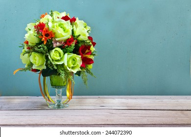 flower bouquet in glass vase on wood table grunge wall