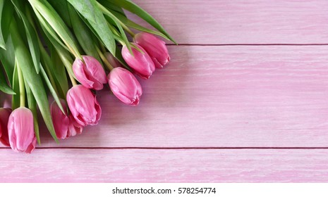 Flower bouquet of pink tulips on a wooden table or wooden planks. Spring background with copy space and pink spring flowers.