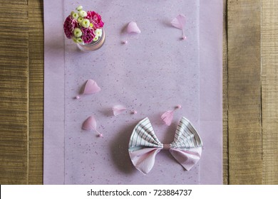 A flower bouquet seen from above and placed on a bright pink tablecloth.