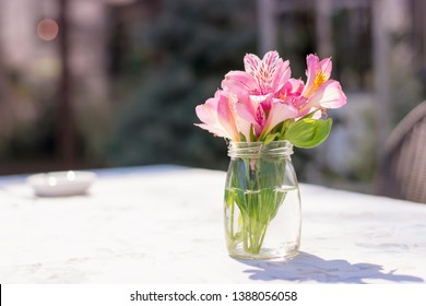 Flower bouquet in a vase on a sunny summer day in cafe