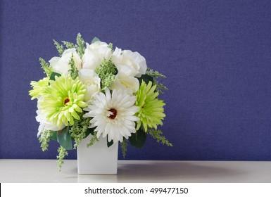 flower bouquet in white vase,purple background.Artificial Flowers.
