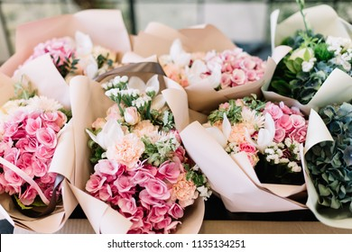 A lot of flower bouquets at the florist shop on the table made of hydrangea, roses, peonies, mattiola, eustoma in pink and sea green colors