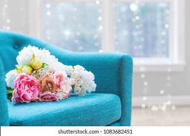 Flower bouquets in large luxury interior home with turquoise chair