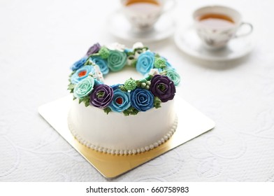 Flower cake with cup of tea on white background