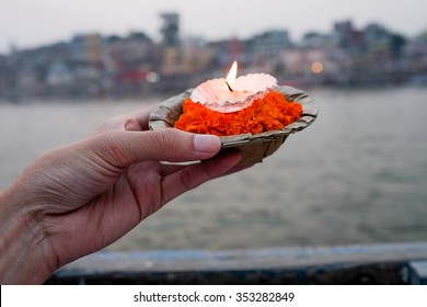 The flower and candle in banana leave vessel . The Buddhist  believe one way to make merit by out this thing floating in the river .