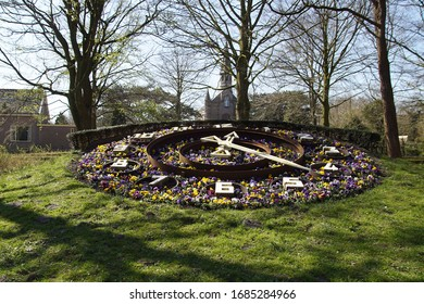 Flower clock with garden pansies in the park Alkmaarderhout of the Dutch city of Alkmaar with a small church in the background. Netherlands, March 26, 2020.