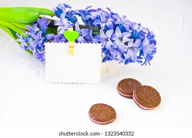 Flower composition. Blue hyacinth lies in the background, a number of dishes and chocolate chip cookies, still life adorn cinnamon sticks. Nearby there is a paper card for a signature decorated with a