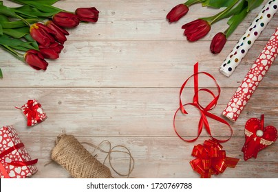 Flower composition. A bouquet of spring red tulips, gift boxes, wrapping paper, ribbons and bows on a light wooden background. Free space.