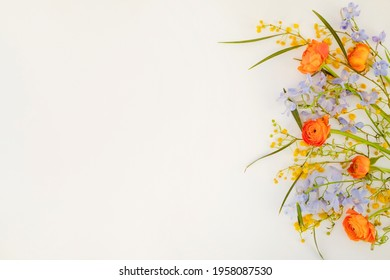 Flower composition with orange ranunculus, blue delphinium and yellow mimosa branches. Visible petal structure. Bright floral arrangement isolated on white. Top view, close up, copy space, background