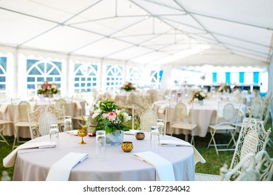 Flower decorations on a celebration table , bright white tent for party's in outdoors.