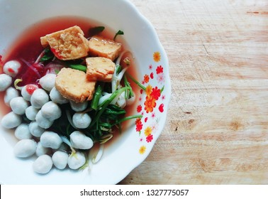 A  flower decotated white bowl of pink fishballs noodles topped with red sauce, small fishball, fried tofu, and vegetable placed on the wood chopping board in Nakorn Sawan, Thailand