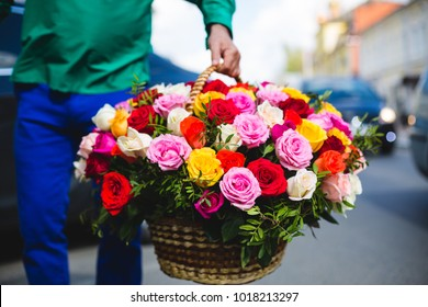 Flower delivery. Man holding a big bouquet of beautiful flowers in a wicker basket