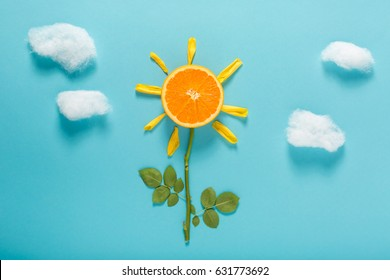 Flower design concept with orange slice and cotton clouds