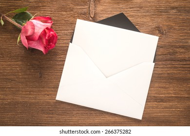Flower and envelope on wooden background