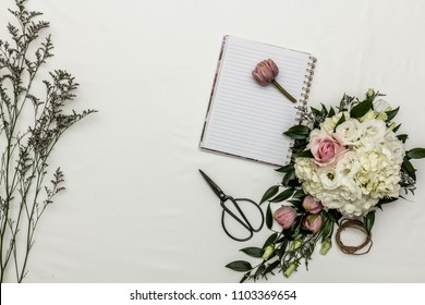 Flower flat lay with notebook and sissors