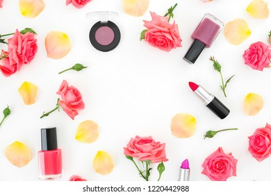 Flower frame of roses flowers, petals and feminine make up cosmetics on white background. Flat lay, top view.