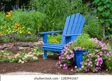 Flower garden with blue Adirondack chair, Butterfly Bushes, Peach and Purple Verbenas, Yellow Lantana, Raspberry Blast petunias and Diamond Frost Euphorbia in blue pot, Marion County, Illinois