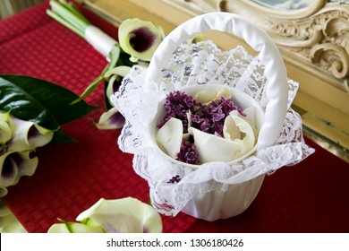 a flower girls white basket full of purple flowers and white rose petals