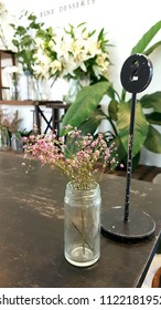 A flower in glass on table in coffee shop.