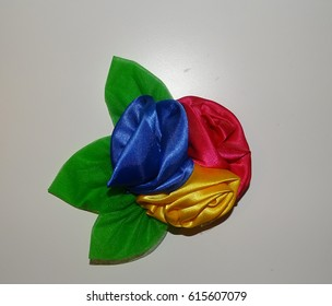 Flower hair bow with green leaves. White background.