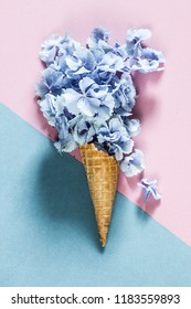 Flower hortensia petals in an ice cream cones on a blue / purple background. Summer refreshment concept. Top view.