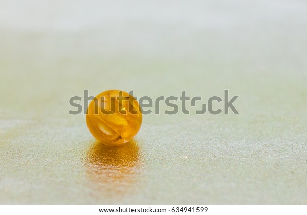 Flower inside of ball shaped crystal made of epoxy resin close-up with bokeh on toned background shallow depth of field